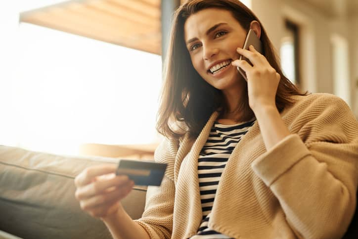 woman on phone with credit card